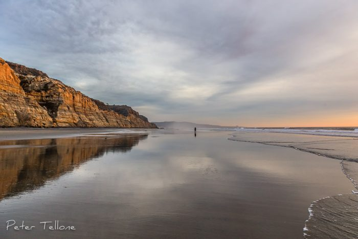 Photo of A man stands alone in reflection on Torrey Pines Beach, La Jolla, California Fine Art print