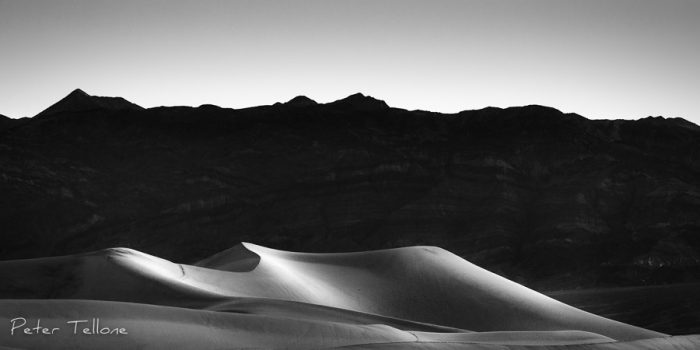 The sun lit sand dunes at Mesquite Flats in Death Valley mimic the shape of a sleeping woman